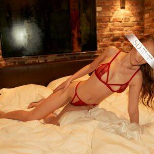Schlanke Frau im Bett trägt rote Dessous