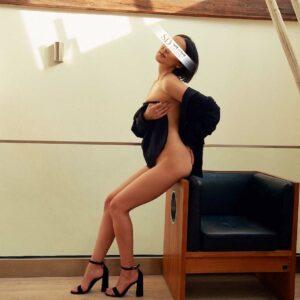 Top Escort Model Ria bedeckt ihren nackten Körper mit einer Jacke
