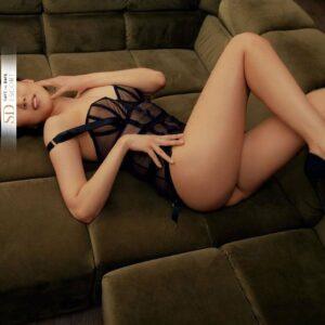 Sinnliche Lady liegt mit High Heels und Lingerie auf einem grünen Sofa